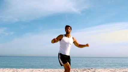 Man jumping with arms up on the beach