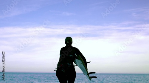 Female surfer running towards the ocean