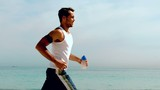 Athletic man jogging across the beach