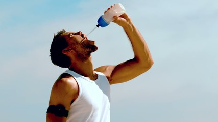 Sportsman rehydrating with water on the beach