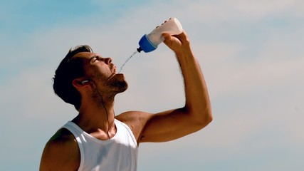 Athletic man rehydrating with water on the beach