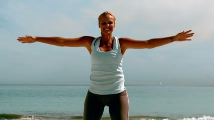 Sportswoman doing jumping jacks on the beach