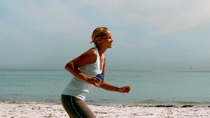 Sportswoman jogging on the beach