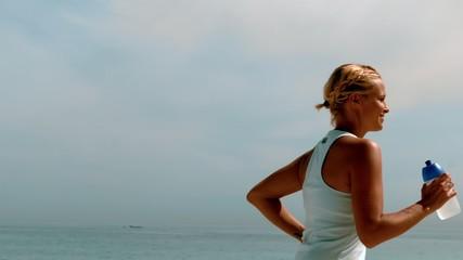 Sportswoman jogging across the beach
