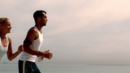 Athletes jogging across the beach