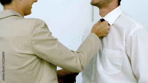Businesswoman helping a man tying his tie