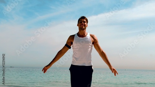 Sportsman doing jumping jacks on the beach