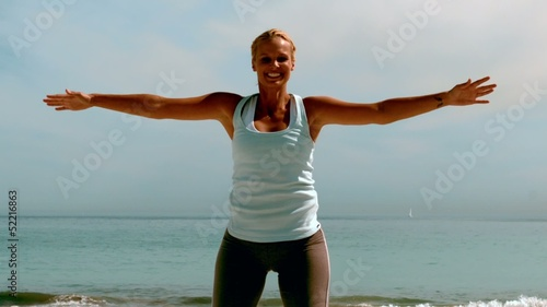 Sportswoman doing jumping jacks on the beach