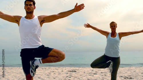 Friends in yoga positions on the beach