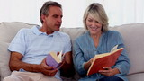 Mature people reading books on the couch