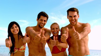 Friends giving thumbs up to the camera at the beach