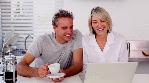 Mature couple using laptop while having a coffee
