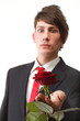 Young man presenting a flower red rose isolated