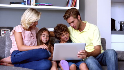 Family on the couch looking at laptop