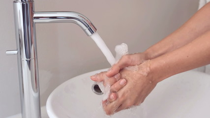 Someone washing their hands at the sink in bathroom