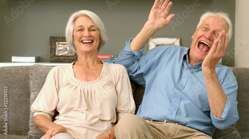 Elderly couple laughing and looking to the camera
