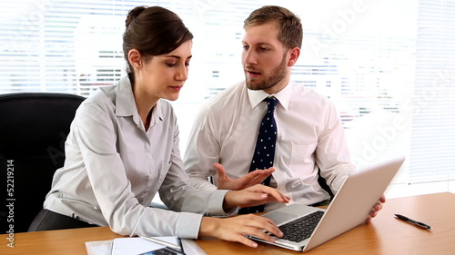 Business partners discussing something on laptop