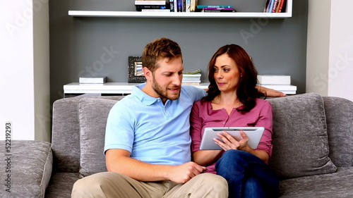Couple using tablet on the couch