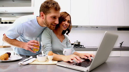 Woman showing her partner something on laptop
