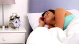 Woman waking up and going back to sleep