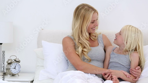 Mother and daughter chatting in bed