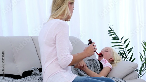 Mother giving her daughter medicine on a spoon