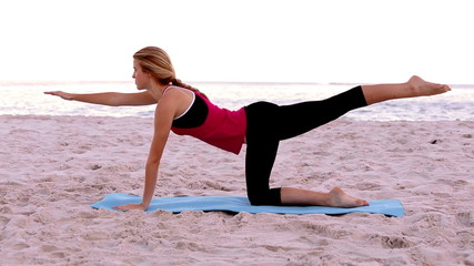 Blonde woman doing pilates stretches