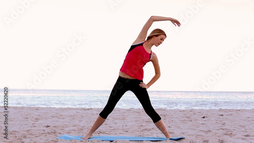 Woman stretching on the beach