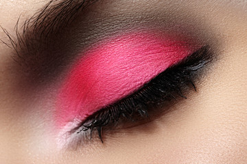 Female eye with celebratory bright pink color eyeshadow
