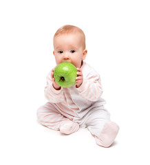 cute happy baby eats fruit green apple isolated