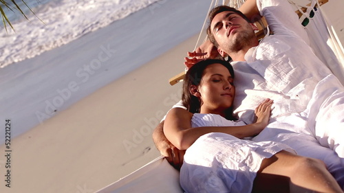 Attractive couple sleeping together in hammock