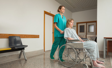 Nurse wheeling the wheelchair of a female patient
