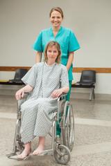 Smiling nurse wheeling a female patient