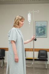 Side view of a female patient walking while holding a drip stand