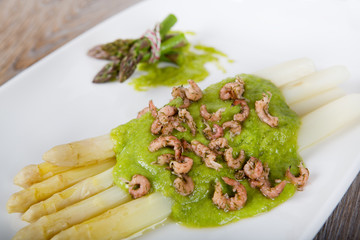 Delicious bunch of white asparagus with green sauce