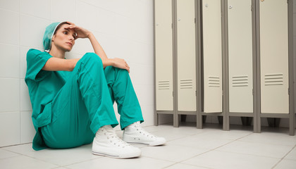 Tired nurse sitting on the floor