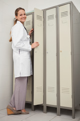 Doctor smiling next to her locker
