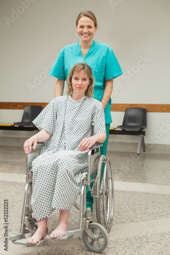 Smiling nurse wheeling a female patient