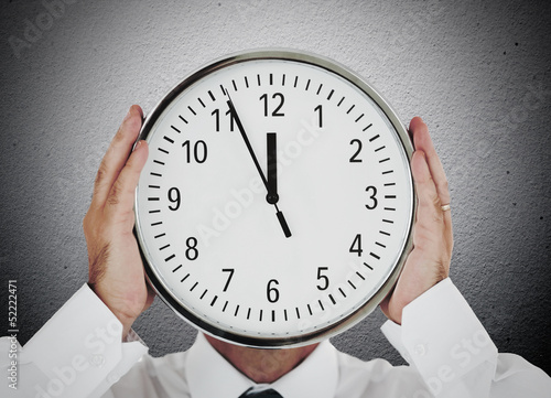 Businessman hiding his face with clock