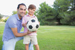 Portrait of father and son with a football