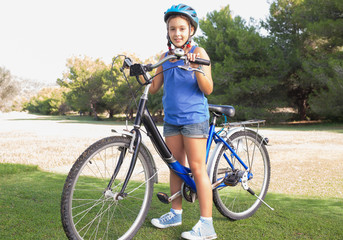 Girl standing with bicycle