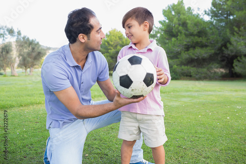 Father and son holding a football