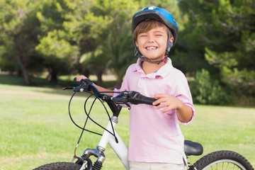 Smiling little boy wearing a helmet with his bike