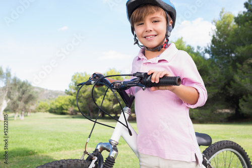 Cute boy wearing helmet and leaning on bike