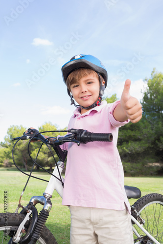 Happy boy giving thumbs up with his bike