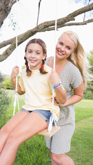 Portrait of happy mother pushing her daughter on a swing