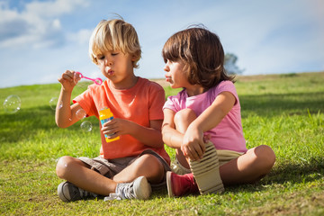 Brother and sister blowing bubbles