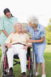 Man in wheelchair chatting with his nurse and partner