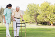 Elderly man walking in park with zimmer frame