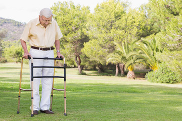 Elderly man using zimmer frame to walk